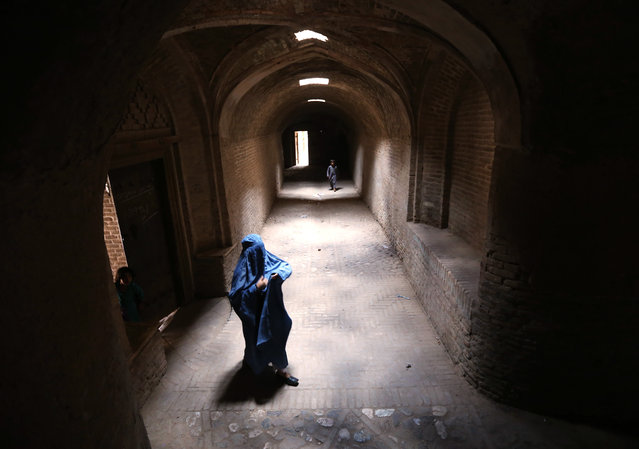 An Afghan woman wearing traditional dress walks through a covered alley way in Herat, Afghanistan, 05 August 2015. Following the partial withdrawal of NATO troops January 2015 Afghanistan has been gripped with ever increasing unrest, as the Government strives to maintain its tenuous grip on areas outside of major conurbations in the face of armed opposition. (Photo by Jalil Rezayee/EPA)