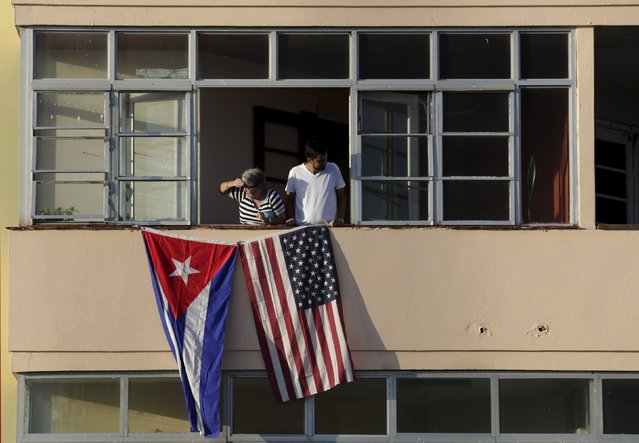 Cuban residents living next to the U.S. embassy look out of their window decorated with the Cuban and U.S. flags in Havana, Cuba, August 14, 2015. U.S. Secretary of State John Kerry travels to Cuba on Friday to raise the U.S. flag at the recently restored American embassy in Havana, another symbolic step in the thawing of relations between the two Cold War-era foes. (Photo by Enrique De La Osa/Reuters)