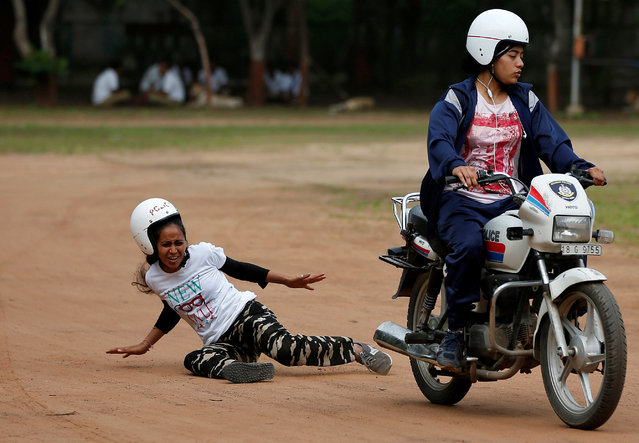 A policewoman reacts as she falls off from a motorcycle while taking part in a rehearsal for Independence Day celebrations, in Ahmedabad, India August 4, 2017. (Photo by Amit Dave/Reuters)