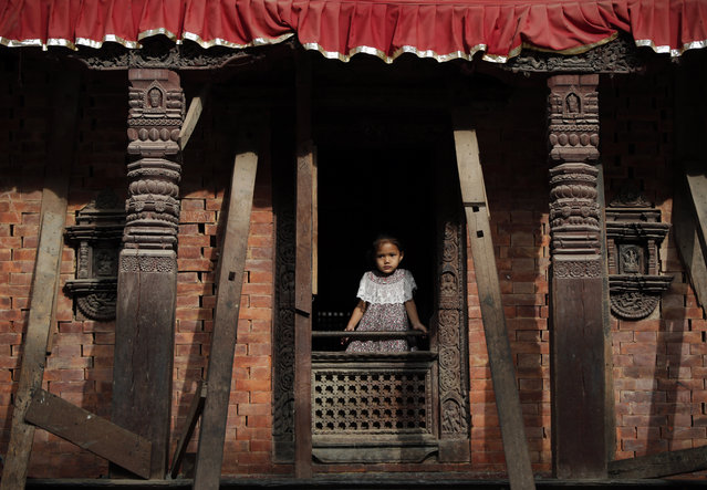 A young Nepalese girl looks out from the window of a temple at Basantapur Durbar Square, Kathmandu, Nepal, Tuesday, August 8, 2017. Basantapur Durbar Square is the plaza in front of the royal palace, a UNESCO World Heritage site, frequented by tourists. (Photo by Niranjan Shrestha/AP Photo)