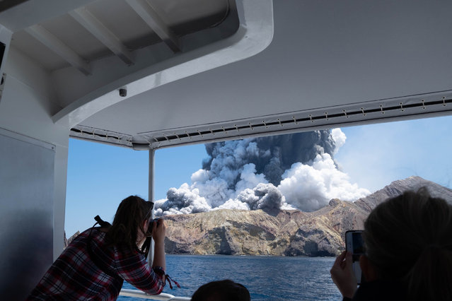 In this December 9, 2019, photo provided by Michael Schade, tourists on a boat look at the eruption of the volcano on White Island, New Zealand. Unstable conditions continued to hamper rescue workers from searching for people missing and feared dead after the volcano off the New Zealand coast erupted in a towering blast of ash and scalding steam while dozens of tourists explored its moon-like surface. (Photo by Michael Schade via AP Photo)