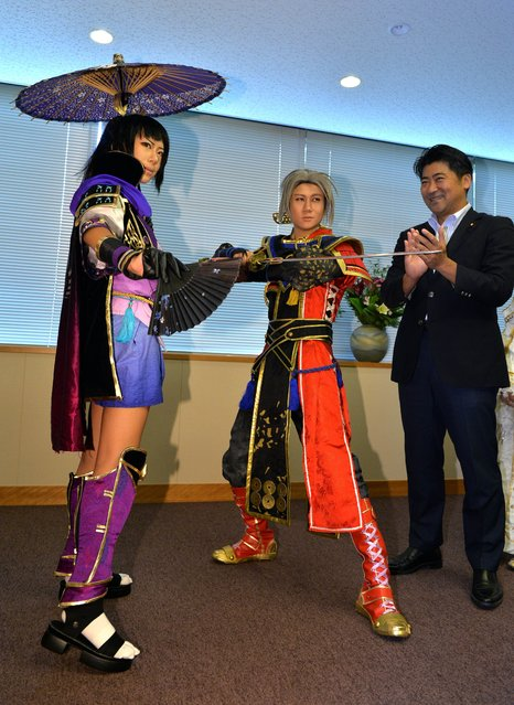 """Japanese Vice Foreign Minister Seiji Kihara (R) claps his hands as participants of the """"World Cosplay Summit 2014"""" Zeng Shengnan of China (L) and Lu Hao of China (C) strike a pose during their courtesy call at Kihara's office in Tokyo on July 30, 2014. Participants from 22 countries, dressed in animation or video game characters, will join the World Cosplay Summit in Nagoya, central Japan on August 2 and 3. (Photo by Yoshikazu Tsuno/AFP Photo)"""