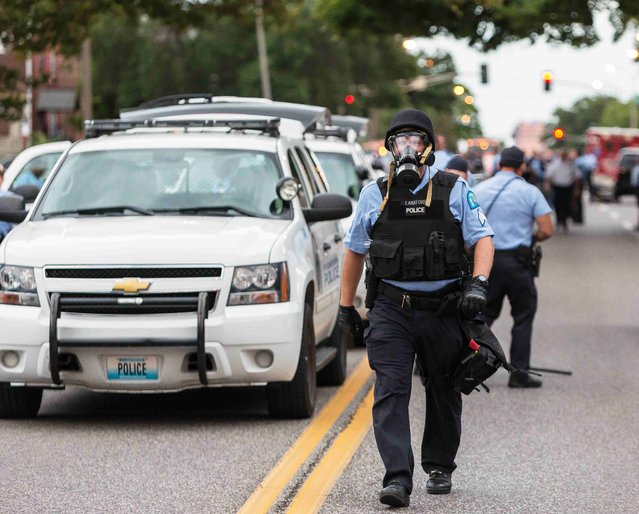 Police wear gas masks as they attempt to disperse a crowd that gathered after a shooting incident in St. Louis, Missouri August 19, 2015. (Photo by Kenny Bahr/Reuters)