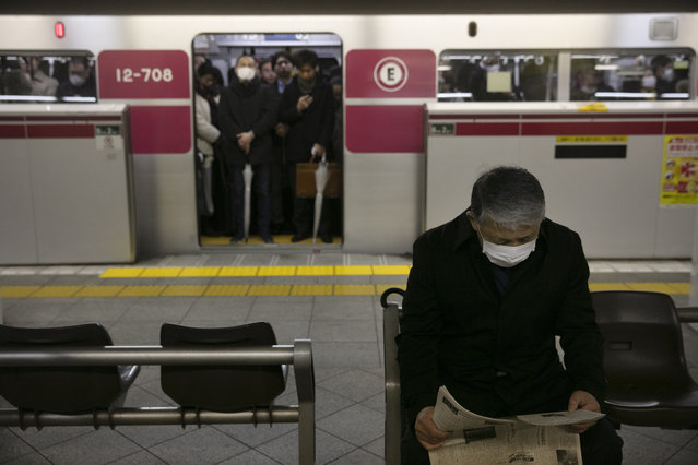 A commuter wearing a mask reads a newspaper while waiting for a train to arrive during morning rush hours Tuesday, January 28, 2020, in Tokyo. China on Tuesday reported 25 more deaths from a new viral disease as the U.S. government prepared to evacuate Americans from the city at the center of the outbreak. Japan, Mongolia, France and other governments also were preparing evacuations. (Photo by Jae C. Hong/AP Photo)