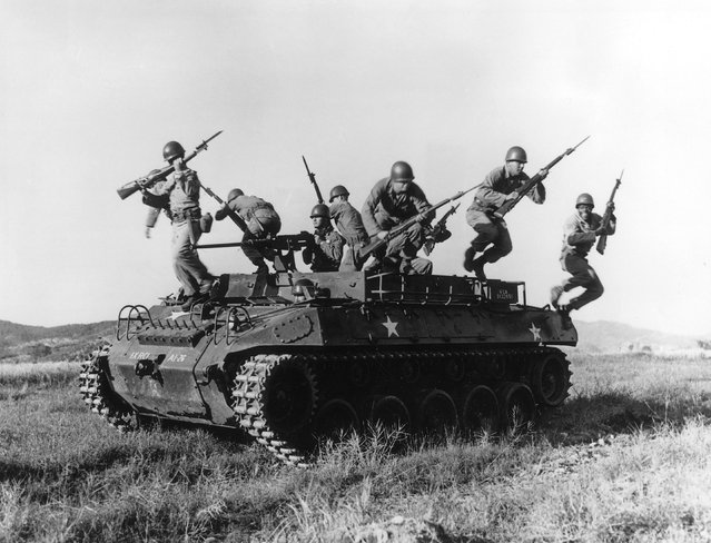 American soldiers leaping from an armoured personnel carrier during exercises in Korea, 17th March 1954.  (Photo by Three Lions)
