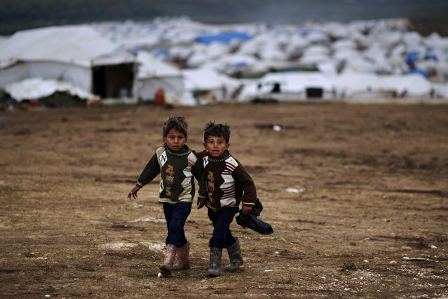 Syrian boys, whose family fled their home in Idlib, walk to their tent, at a camp for displaced Syrians, in the village of Atmeh, Syria, Monday, December 10, 2012. (Photo by Muhammed Muheisen/AP Photo)