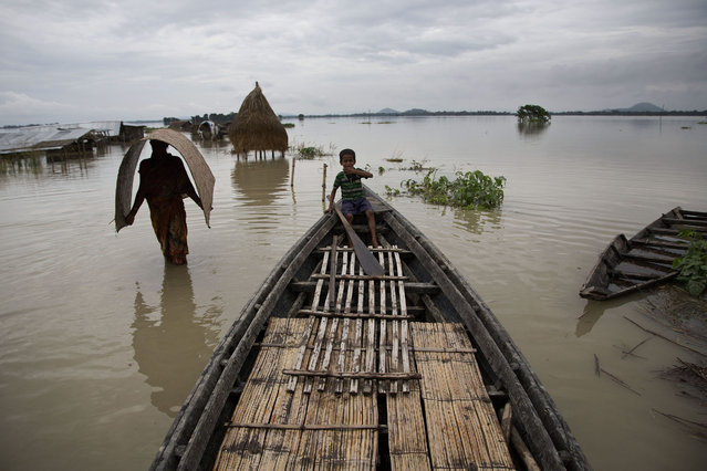 Indian villagers affected by monsoon rains move through a flooded area in Morisuti village, about 65 kilometers (40 miles) east of Gauhati, India, Sunday, August 23, 2015. (Photo by Anupam Nath/AP Photo)