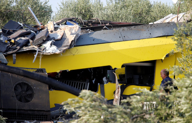 A man looks at the wreckage at the site where two passenger trains collided in the middle of an olive grove in the southern village of Corato, near Bari, Italy, July 12, 2016. (Photo by Alessandro Garofalo/Reuters)