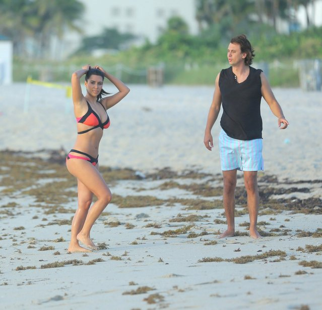 Kim Kardashian surfs up an impressive sight as she wanders along a Miami beach in a colourful bikini on August 4, 2012. The reality TV star looked stunning as she wandered barefoot along the shore in the black and orange two-piece