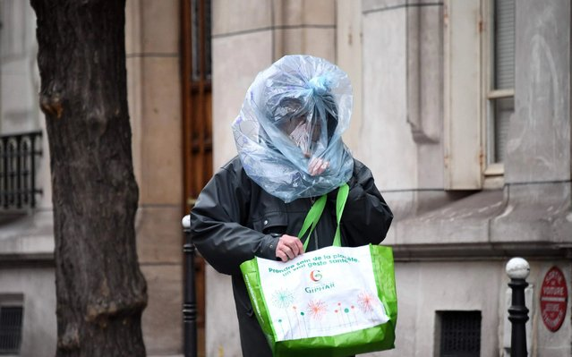 A man protect his face with a plastic bag as he walks in the street in Paris on March 21, 2020 as a strick lockdown comes into in effect to stop the spread of the COVID-19 in the country. French President asked people to stay at home to avoid the spreading the Covid-19, saying only necessary trips would be allowed and violations would be punished. The country has already shut cafes, restaurants, schools and universities and urged people to limit their movementnon-essential public places including restaurants and cafes. (Photo by Franck Fife/AFP Photo)