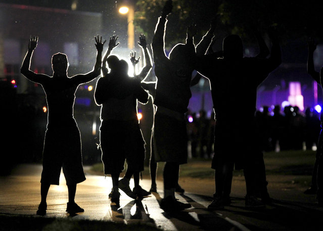 People raise their hands in the middle of the street as police wearing riot gear move toward their position trying to get them to disperse Monday, August 11, 2014, in Ferguson, Mo. The FBI opened an investigation Monday into the death of 18-year-old Michael Brown, who police said was shot multiple times Saturday after being confronted by an officer in Ferguson. (Photo by Jeff Roberson/AP Photo)
