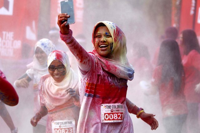 "A participant takes a selfie as she runs through a ""color station"" during the five-kilometer color run event in Kuala Lumpur, Malaysia, Sunday, August 17, 2014. (Photo by Lai Seng Sin/AP Photo)"