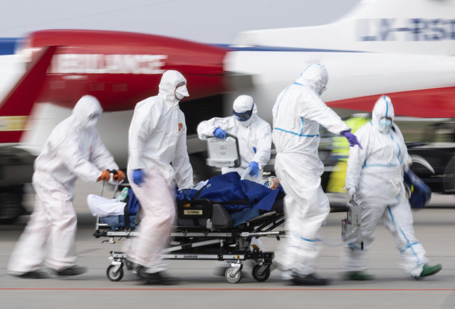 A patient from France who is seriously ill with the coronavirus is transported from an ambulance plane after landing at Dresden International Airport in Dresden, Germany, Saturday, April 4, 2020.(Photo by Robert Michael/dpa via AP Photo)