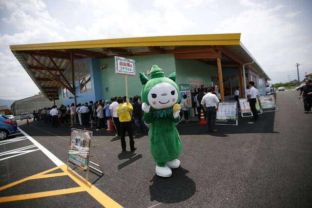 People wait outside a pachinko parlour as a person dressed as Dynam's official mascot, Morisuke, tries to attract visitors in Fuefuki, west of Tokyo June 19, 2014. (Photo by Issei Kato/Reuters)
