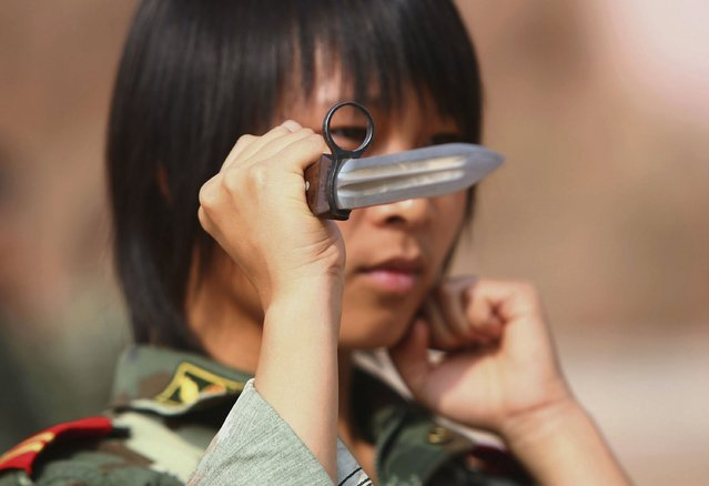 A member of a female grappling team from Qinghai Province armed police undergoes dagger exercise on August 8, 2006 in Xining of Qinghai Province, China. The female grappling team, established in May 2006, has 40 women soldiers aged 18 to 21. The training program includes grappling, boxing, dagger exercise and shooting.  (Photo by China Photos/Getty Images)