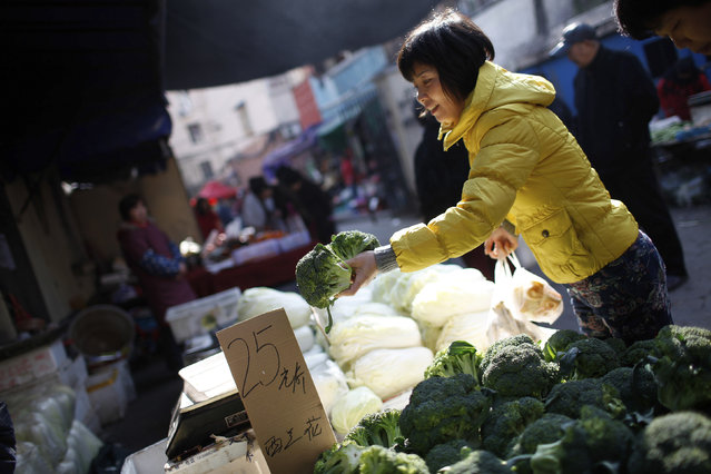A woman holds up cauliflowers at a stall inside a market in Shanghai December 9, 2011. China's annual inflation rate tumbled in November to 4.2 percent, the lowest level in more than a year, fuelling expectations of further monetary policy easing to combat deteriorating domestic and international economic conditions. The rate has dropped rapidly since hitting a three-year high of 6.5 percent in July and is now at a pace closer to the full-year government target for 2011 of 4 percent. (Photo by Aly Song/Reuters)