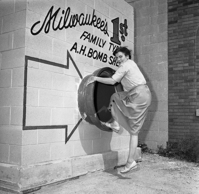 Mrs. Marie Graskamp of Milwaukee shows the different positions one might assume when entering the bomb shelter in Milwaukee  September 3, 1958. This circular entrance is about three feet in diameter. This is the entrance (according to the builders) that would connect to the cellar of a home assuming the shelter was in the ground for added protection. (Photo by AP Photo)
