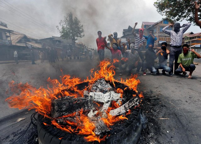 Masked demonstrators shout slogans next to a burning tyre during a protest in Srinagar against the recent killings in Kashmir, July 26, 2016. (Photo by Danish Ismail/Reuters)