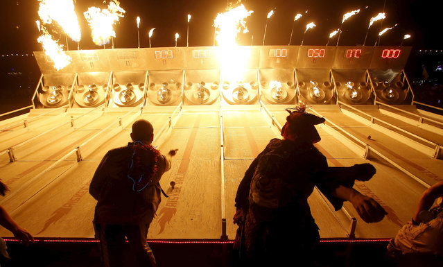"People play a game of flaming skee-ball at the Charcade during the Burning Man 2015 ""Carnival of Mirrors"" arts and music festival in the Black Rock Desert of Nevada, September 1, 2015. (Photo by Jim Urquhart/Reuters)"