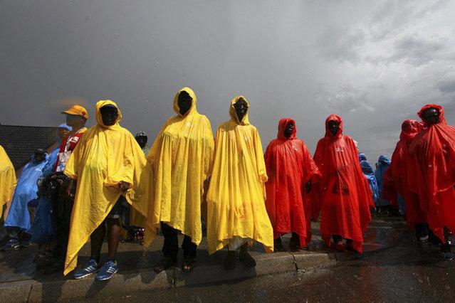 Pilgrims covered in raincoats wait for Pope Francis at the Campus Misericordiae during World Youth Day in Brzegi near Krakow, Poland July 31, 2016. (Photo by Kuba Ociepa/Reuters/Agencja Gazeta)