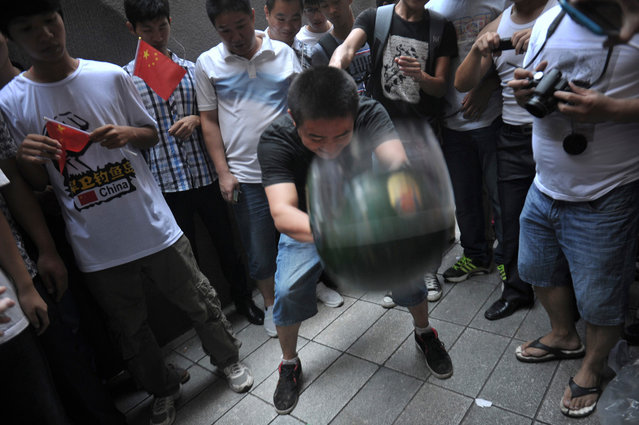 A protester throws a police helmet to the ground as fellow demonstrators take pictures during an anti-Japan protest in Guangzhou, Guangdong province, on September 16, 2012. (Photo by Reuters/Stringer)