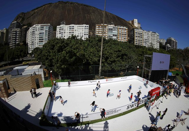 People use adapted ice skates to skate on an artificial ice rink at the Switzerland house in Lagoa, Rio de Janeiro, Brazil on August 1, 2016. (Photo by Ivan Alvarado/Reuters)