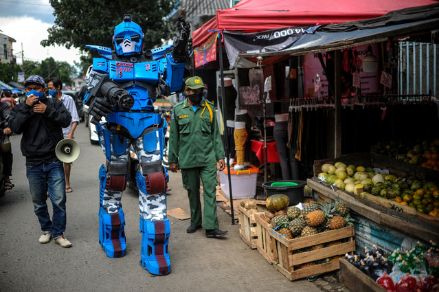 A man wearing a Transformers costume appeals to the citizens to stay at a home amid coronavirus disease (COVID-19) outbreak, in Bandung, West Java Province, Indonesia, May 4, 2020. (Photo by Raisan Al Farisi/Antara Foto via Reuters)