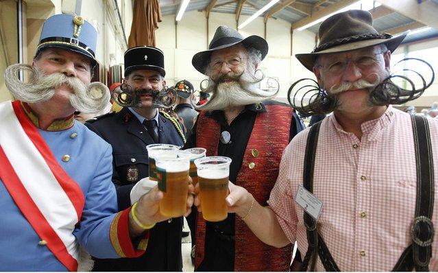 Participants have a beer as they take part in the 2012 European Beard and Moustache Championships in Wittersdorf near Mulhouse, Eastern France, September 22, 2012. More than a hundred participants competed in the first European Beard and Moustache Championships organized in France. (Photo by Vincent Kessler/Reuters)