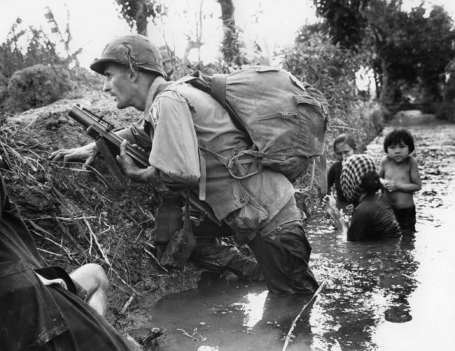 In this January 1, 1966 file photo, a Paratrooper of the 173rd U.S. Airborne brigade crouches with women and children in a muddy canal as intense Viet Cong sniper fire temporarily pins down his unit during the Vietnamese War near Bao trai in Vietnam. Filmmaker Ken Burns said he hopes his 10-part documentary about the War, which begins Sept. 17, 2017 on PBS, could serve as sort of a vaccine against some problems that took root during the conflict, such as a lack of civil discourse in America. (Photo by Horst Faas/AP Photo)