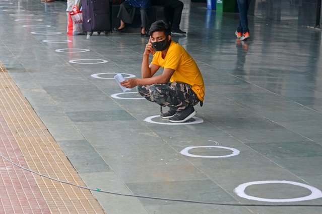 A passenger sits in a marked circle to maintain social distancing as he waits for the train to arrive at New Jalpaiguri railway station on the outskirts of Siliguri on May 13, 2020. India's enormous railway network tentatively ground back to life on May 12 as a gradual lifting of the world's biggest coronavirus lockdown gathered pace even as new cases surged. (Photo by Diptendu Dutta/AFP Photo)