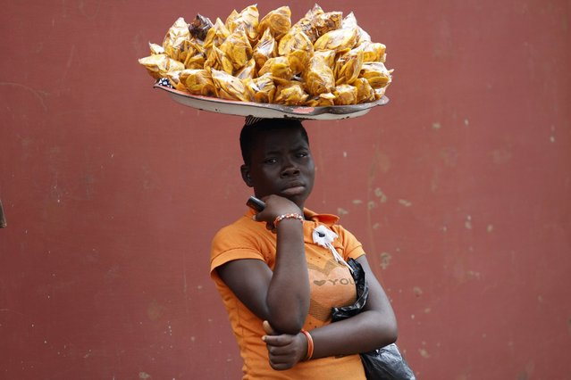 A girl hawks plantain chips in the Ikotun-Egbe neighbourhood of Nigeria's commercial capital Lagos, September 17, 2014. (Photo by Akintunde Akinleye/Reuters)