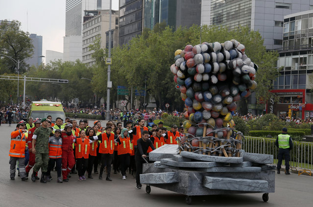 Rescue workers and volunteers that participated in rescue operations after the Sept. 19 earthquake, march behind a fist made out of safety helmets, as they lead the Day of the Dead parade on Mexico City's main Reforma Avenue, Saturday, October 28, 2017. (Photo by Eduardo Verdugo/AP Photo)