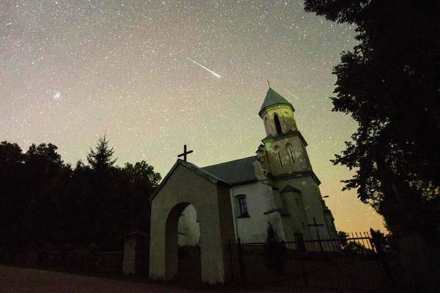 A Perseid meteor crosses the sky over the medieval Saint Kazimir Catholic church at night in the village of Vselyub some 125 km west of Minsk, on August 13, 2016. (Photo by AFP Photo/Stringer)