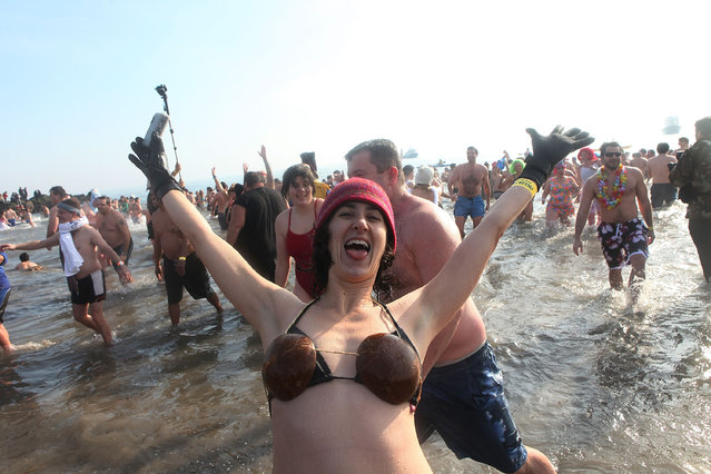 A woman celebrates after participating in the annual Coney Island Polar Bear Club New Year's Day swim at Coney Island on January 1, 2011 in the Brooklyn borough of New York City. The Coney Island Polar Bear Club claims itself as the oldest winter bathing organization in the U.S. and attracts hundreds to the beach for the annual swim in the Atlantic Ocean. (Photo by Andrew Burton)
