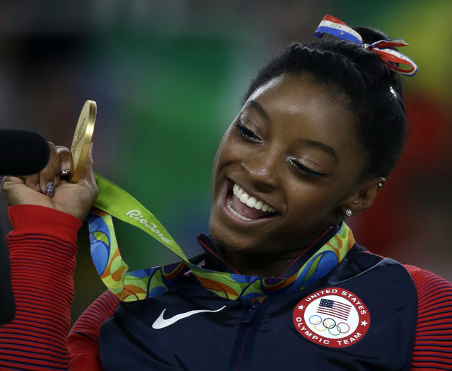 United States' Simone Biles displays her gold medal for floor during the artistic gymnastics women's apparatus final at the 2016 Summer Olympics in Rio de Janeiro, Brazil, Tuesday, August 16, 2016. (Photo by Rebecca Blackwell/AP Photo)
