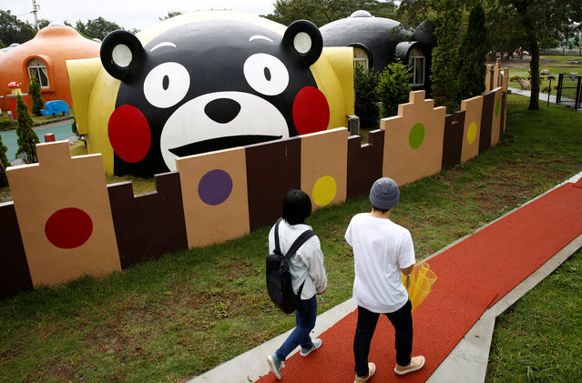 """Visitors walk past a quake-resistant dome house. """"We were looking for something very Japan and different that would just be fun"""", said Singaporean tourist Tsalina Phang, who was staying in a dome house with her two daughters and husband. """"This, with all the decorations of Kumamon, just sounded perfect for us"""", Phang said, as one of her daughters bounced happily on a bed in front of an image of a red-cheeked bear. (Photo by Kim Kyung-Hoon/Reuters)"""