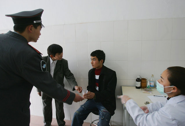 A Chinese boy (C) receives treatment after fainting after refusing to eat at an assistance center February 23, 2005 in Shenzhen, Guangdong Province, China. (Photo by Cancan Chu/Getty Images)
