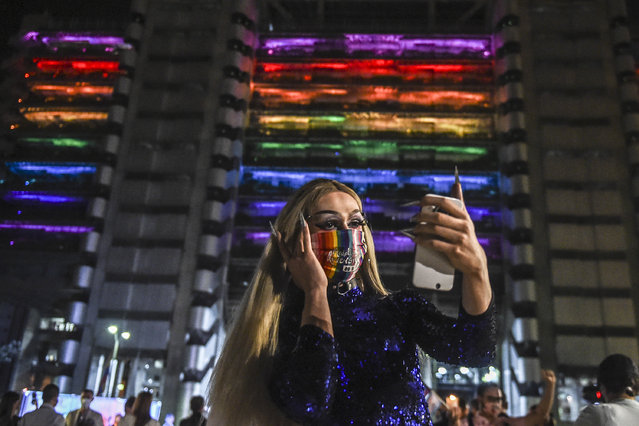 A transgender woman takes a selfie in front of the Empresas Publicas de Medellin (EPM) building illuminated with rainbow colors for Pride Month, amid de COVID 19 pandemic, in Medellin, on June 24, 2020. (Photo by Joaquin Sarmiento/AFP Photo)
