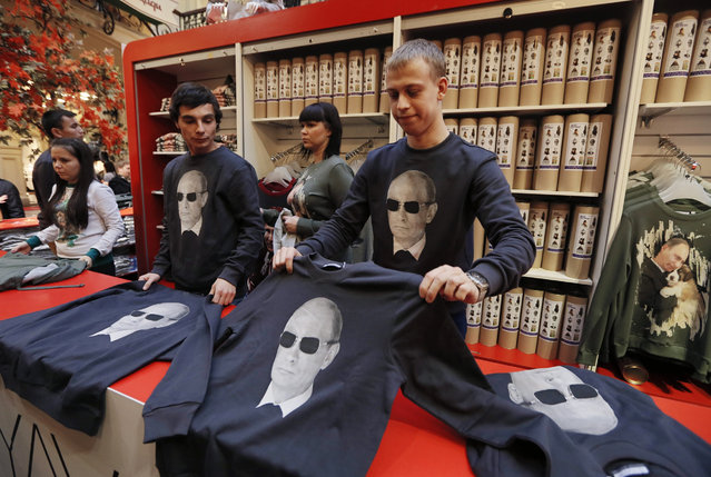 Salesman show sweatshirts with printed portraits of Russian President Vladimir Putin in the GUM department store in Moscow, Russia, 06 October 2014. The Anyavanya brand of Russian designers Anna Yefremova and Ivan Yershov presented the new collection of sweatshirt decorated by Putin prints. (Photo by Yuri Kochetkov/EPA)