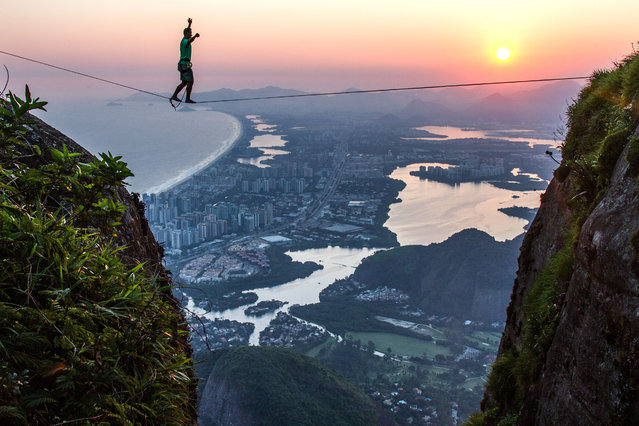 Brave slackliners have been pictured walking the ropes above Rio de Janeiro, Brazil on August 15, 2016, with the half a mile drop showing the city in all its glory. The stunning shots show the daredevils tread across an eighty-two-foot-long high line on Pedra da Gvea mountain with an amazing sunrise illuminating the city landscape behind. (Photo by Rafael Moura/Caters News Agency)