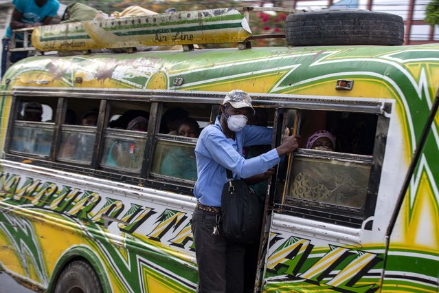 A masked passenger hangs from the side of a bus in Petion-Ville, Haiti, Tuesday, April 7, 2020. To help contain the spread of the new coronavirus, the mayor of Petion-Ville announced public markets will reduce their operation to three days a week, public transportation will limit passengers to eight per mini-bus and Tap-tap vehicles, which very few drivers are enforcing, and passengers are required to wear face masks. (Photo by Dieu Nalio Chery/AP Photo)