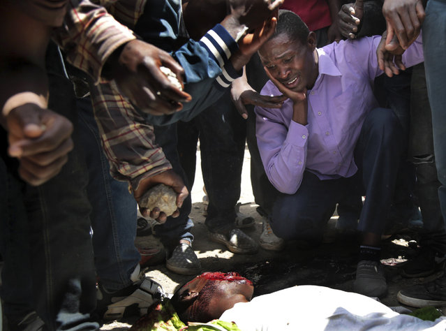 """Opposition supporters react near the body of a man allegedly killed by a stray bullet fired by police, during clashes in the Jacaranda grounds quarter in Nairobi, Kenya, Tuesday, November 28, 2017. Kenyan President Uhuru Kenyatta was sworn in for a second term Tuesday in front of tens of thousands who gathered to celebrate what they hoped would be the end of months of election turmoil, which Kenyatta said stretched the country """"almost to the breaking point"""". (Photo by Brian Inganga/AP Photo)"""