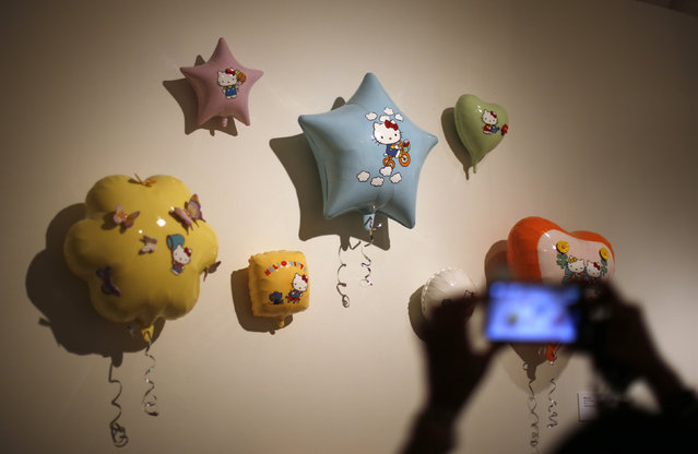 """A woman photographs an exhibit at the """"Hello! Exploring the Supercute World of Hello Kitty"""" museum exhibit in honor of Hello Kitty's 40th anniversary, at the Japanese American National Museum in Los Angeles, California October 10, 2014. (Photo by Lucy Nicholson/Reuters)"""
