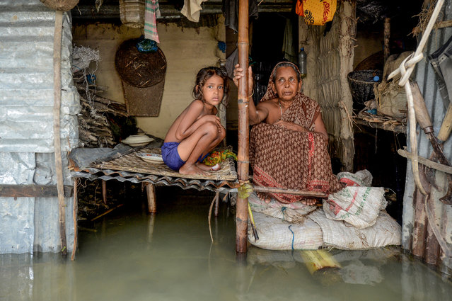 A woman and a young girl sit in their flooded house in Sunamganj on July 16, 2020. (Photo by Munir Uz Zaman/AFP Photo)