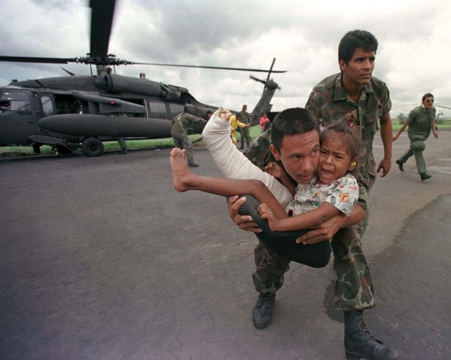 A Nicaraguan soldier carries 5-year-old Wendy Dinosta from a U.S. Blackhawk helicopter after she was evacuated with a broken femur from the north-eastern town of Wiwili, Nicaragua, November 5, 1998. Wiwili, like many other Nicaraguan towns, was completely cut off from the rest of the country and accessible only by helicopter, after devastating flooding destroyed roads and bridges and more than 1,000 houses. The U.S. helicopter is taking part in aid flights to deliver food and other essential supplies. (Photo by Andrew Winning/Reuters)