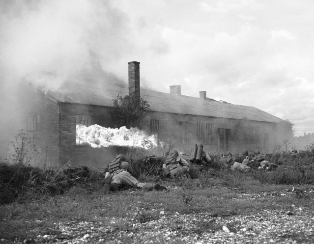 The U.S. forces in Britain have held their first manoeuvres which stressed the use of chemical warfare. One of the infantry units was attacked by enemy planes which dropped smoke bombs to break up their fire power and also simulated mustard gas. Mechanized troops, including scouts on motor-cycles jeeps and scout cars were thrown into the attack and flame throwers were used to clean out strong points to give the American troops a taste of modern warfare. (Photo by AP Photo)