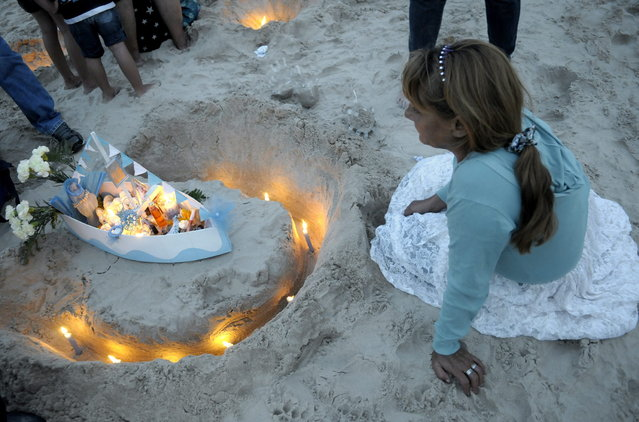 A woman prepares an offering for Yemanja, the African sea goddess, during a ceremony honoring the deity in Montevideo, Uruguay, Saturday, February 2, 2013. Thousands of worshippers come to the beach in Montevideo on her feast day, February 2, bearing candles, flowers, perfumes and and fruit to show their gratitude for her blessings bestowed upon them. The belief in the goddess sprouts from Umbanda, a blend of religions that include African, Catholicism and Spiritism. (Photo by Matilde Campodonico/AP Photo)