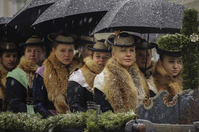 Young girls wearing traditional Bavarian folk outfits sit atop a carriage for the annual Leonhardifahrt procession in Bavaria on November 6, 2014 in Bad Toelz, Germany. The procession honors St. Leonhard, the patron saint of animals used in agriculture, especially horses, in a tradition going back at least to the 15th century. (Photo by Philipp Guelland/Getty Images)