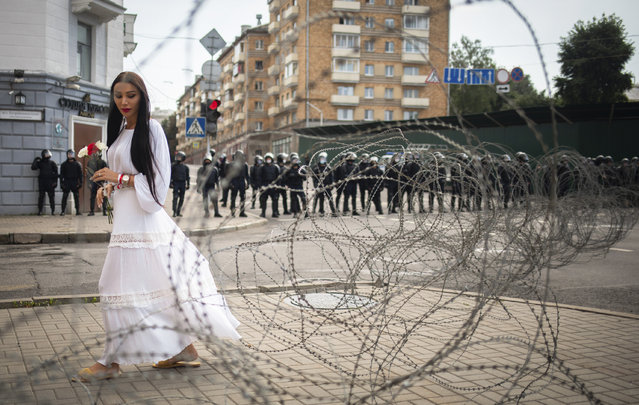 A woman walks past the barbed wire separating Belarusian servicemen and Belarusian opposition supporters during a rally in Minsk, Belarus, Sunday, August 30, 2020. Tens of thousands of demonstrators have gathered in the capital of Belarus, beginning the fourth week of daily protests demanding that the country's authoritarian president resign. The protests began after an Aug. 9 presidential election that protesters say was rigged and officials say gave President Alexander Lukashenko a sixth term in office. (Photo by Tut.By via AP Photo)