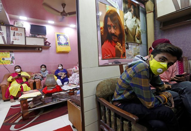 Clients wearing protective face mask wait to meet Sanjay Sharma, a mystic healer and astrologer, at his office in New Delhi, India on August 22, 2020. (Photo by Adnan Abidi/Reuters)